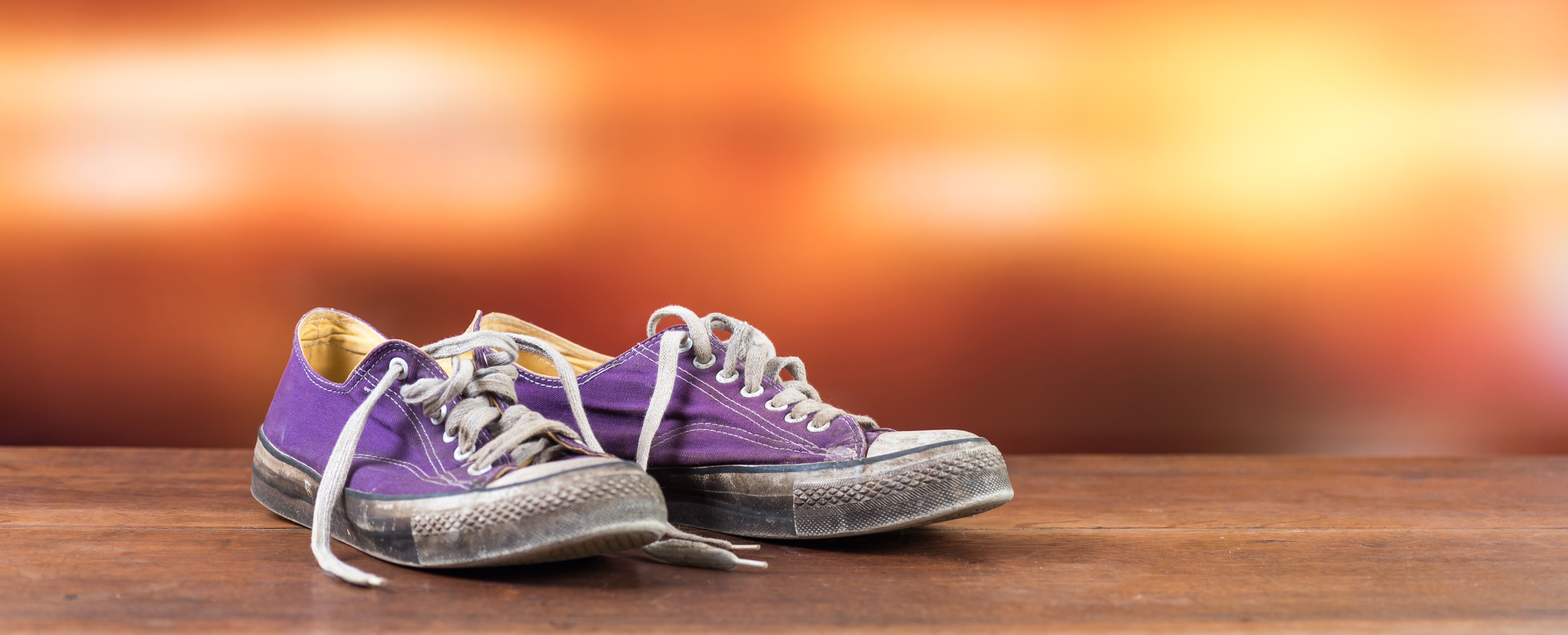 Old used purple sneakers on blurred background